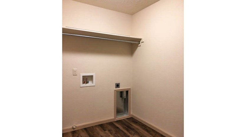 The laundry room in 164 Winter Hawk has space for a washer & dryer to sit side by side, as well as a shelf & hanging bar.