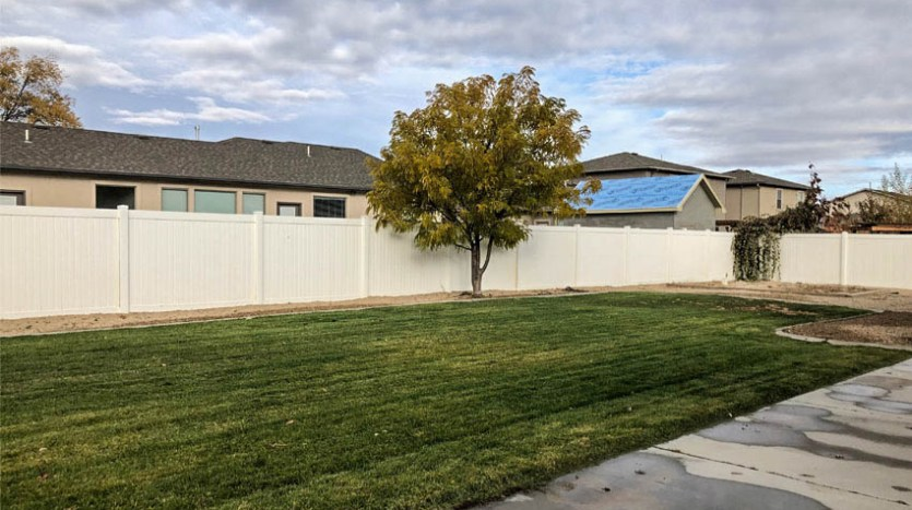 Big backyard including grass, mature landscaping, and a garden area