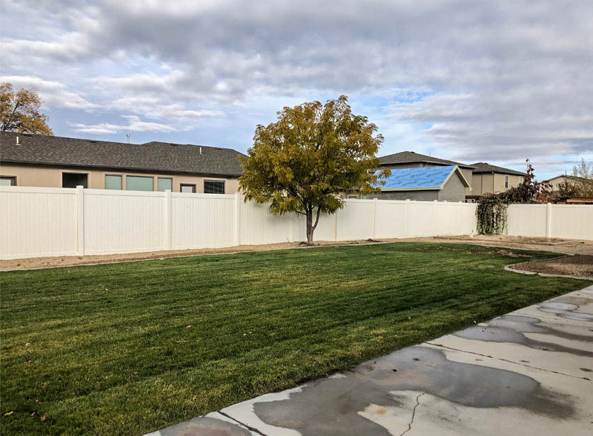 Big backyard including grass, mature landscaping, and a garden area