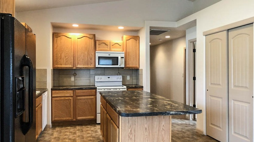 The kitchen of 191 Winter Hawk includes all appliances, a storage isnland with breakfast bar, and a small pantry.