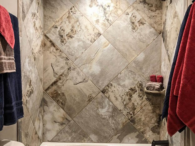 The in-tub shower has custom tile work, a corner shelf, and easy access to both a towel bar and robe hook.
