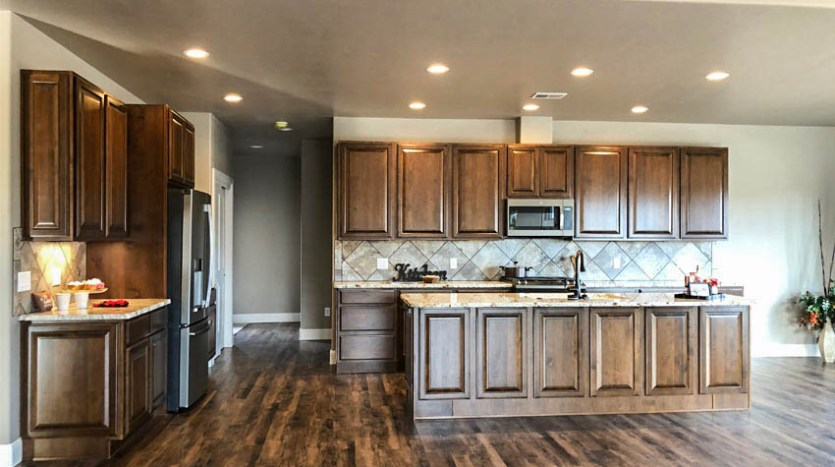 Kitchen of 1329 Niblick Way has an island breakfast bar, wood cabinetry, granite counters, and custom tiled backsplash.