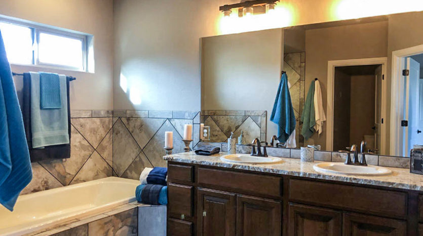 The Master Bath in 1329 Niblick Way includes a large storage vanity with double sinks, a soaking tub, roll-in shower, and private toilet room.