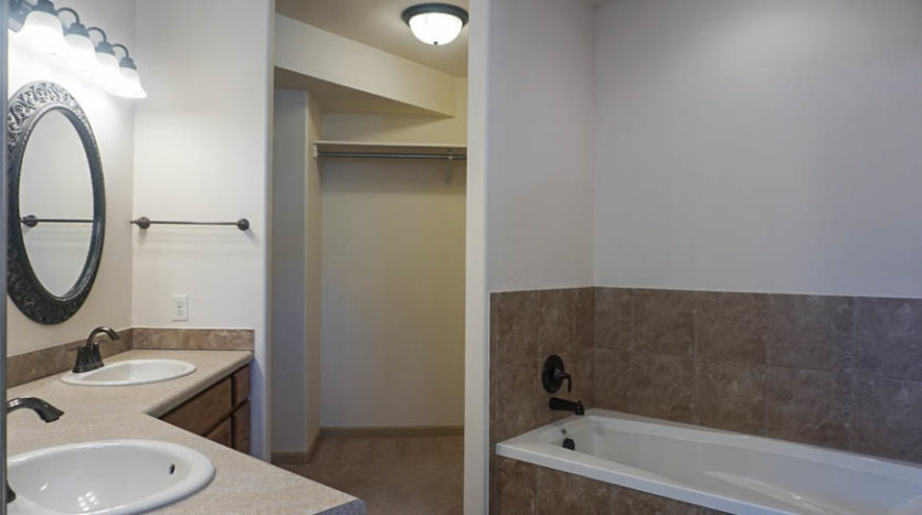 The master bath has a large vanity area with double sinks, and a rectangular soaking tub, step-in shower, and toilet.