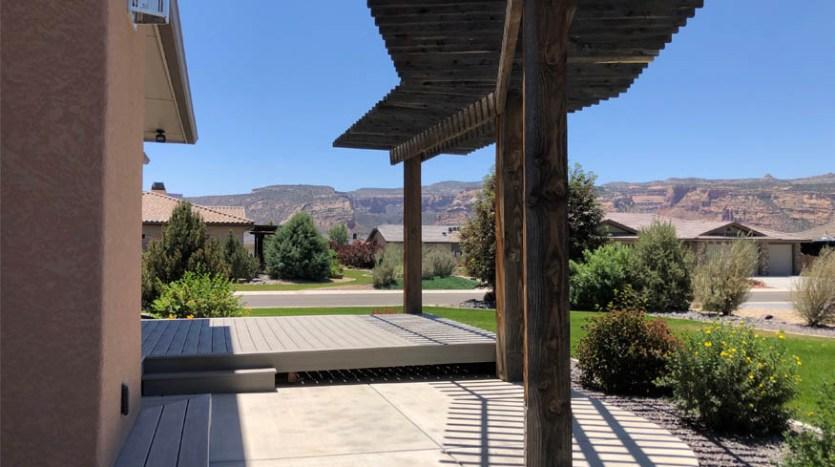 The back patio of 1485 Adobe Falls Way has a rough hewn cedar pergola.