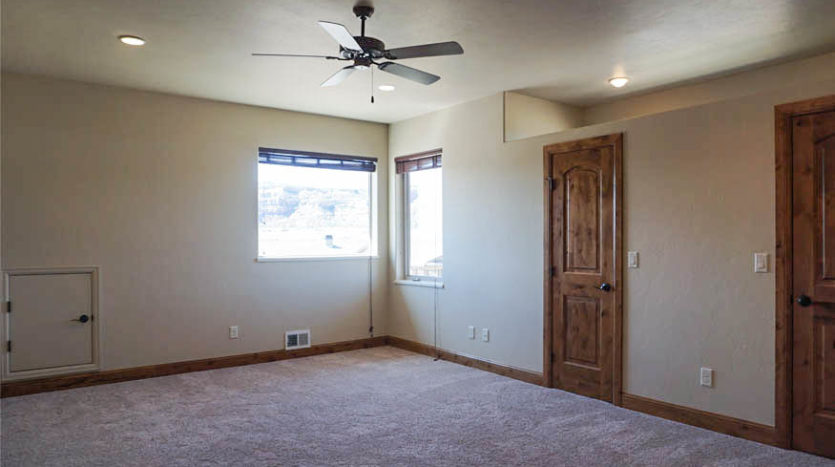 The south west bedroom has double closets, large windows looking out at the Colorado National Monument, recessed lighting, and a ceiling fan.
