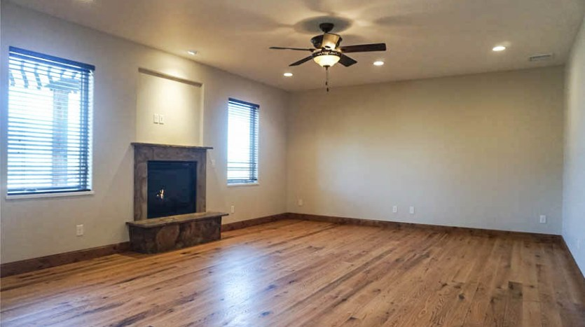 The den has a gas fireplace, hardwood floors, a lighted ceiling fan, and west-facing windows with 2