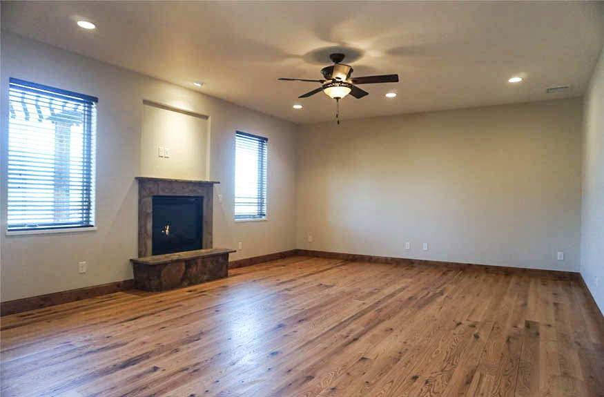"""The den has a gas fireplace, hardwood floors, a lighted ceiling fan, and west-facing windows with 2"""" wood-look blinds."""