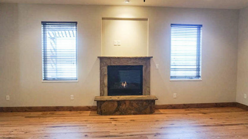 The gas fireplace in the den of 1485 Adobe Falls Way is flanked by west-facing windows.