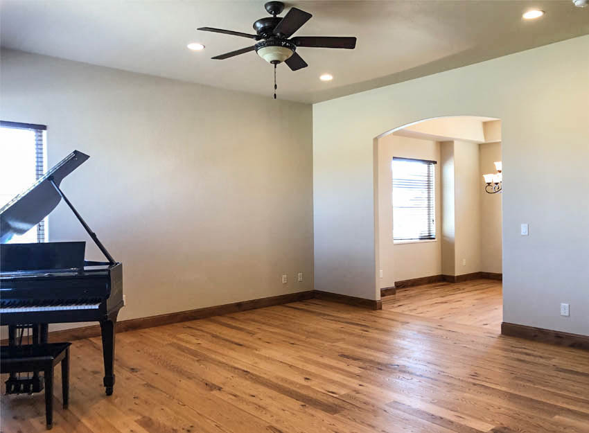 The living room of 1485 Adobe Falls Way has solid hickory floors, a lighted ceiling fan, recessed lighting, and large windows.