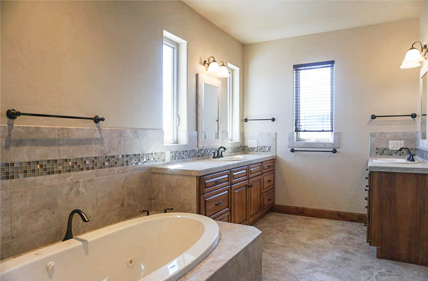 The master bath of 1485 Adobe Falls Way has a jetted tub with custom tile surround, casement windows for fresh air, double storage vanities, and a glass enclosed shower.