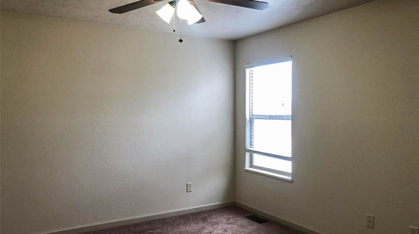 The 2nd bedroom in 170 Sun Hawk has an east facing window and lighted ceiling fan.