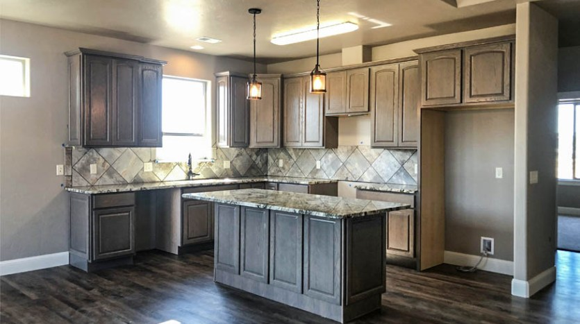 The kitchen of 1484 Shoreline has soft close cabinets, drop lights over the cabinets, under cabinet lighting, and granite countertop. The appliances are set to be delivered in August.