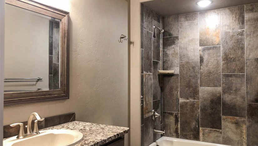 The hall bath of 1446 Shoreline has custome tile work in the shower and granite countertops on the storage vanity.