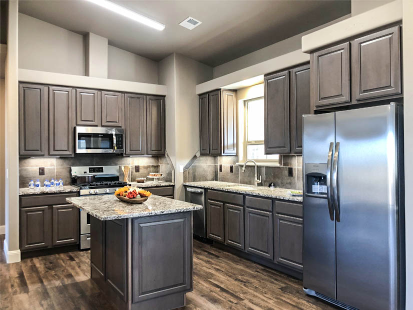 The kitchen of 1446 Shoreline Dr. has soft close cabinetry, under cabinet lighting, custom tiled backsplash, storage island with a bar area, walk-in pantry, and includes the stainless steel appliances.