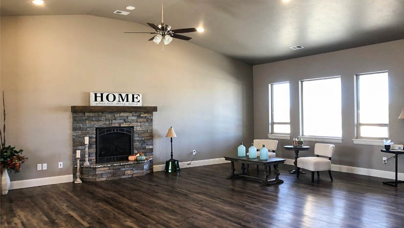 The living room includes a gas fireplace and large windows to let in natural light.