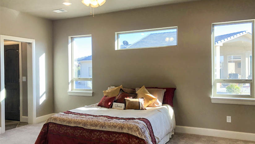 The master bedroom has large windows for natural light, access to the covered back patio, a 5-piece bath, and dual walk-in closets
