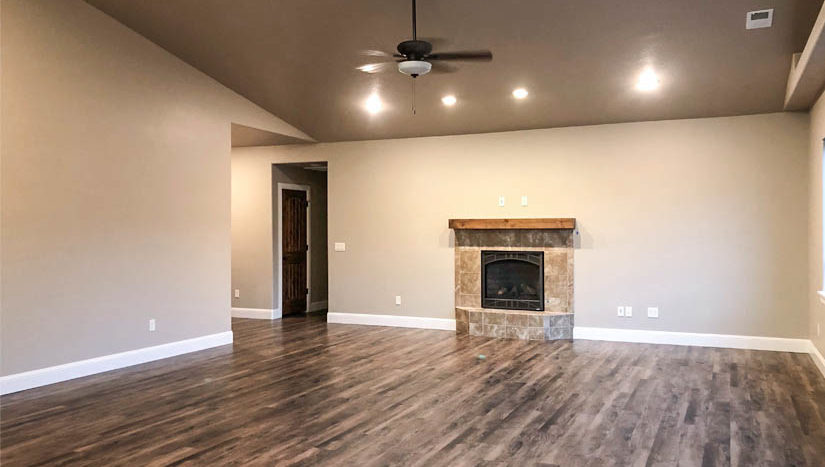 The living room of 1404 Shoreline Drive has a gas fireplace with custom tiled surround and a bespoke built wood mantle.