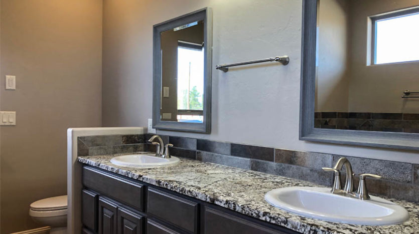 The double sink vanity has a granite countertop, and the toilet is behind a half wall, affording it some privacy.