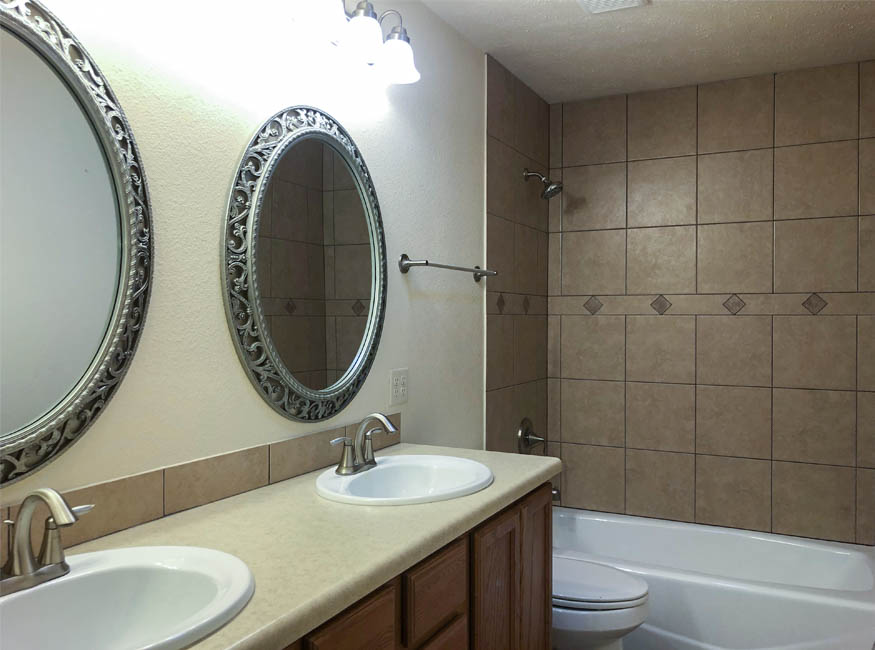 The upstairs hall bath has a double sink vanity, toilet, and in-tub shower.