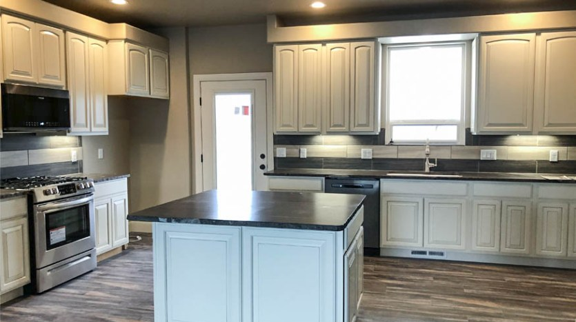 The white cabinets and dark countertops are enhanced by the greige walls and LVP flooring.