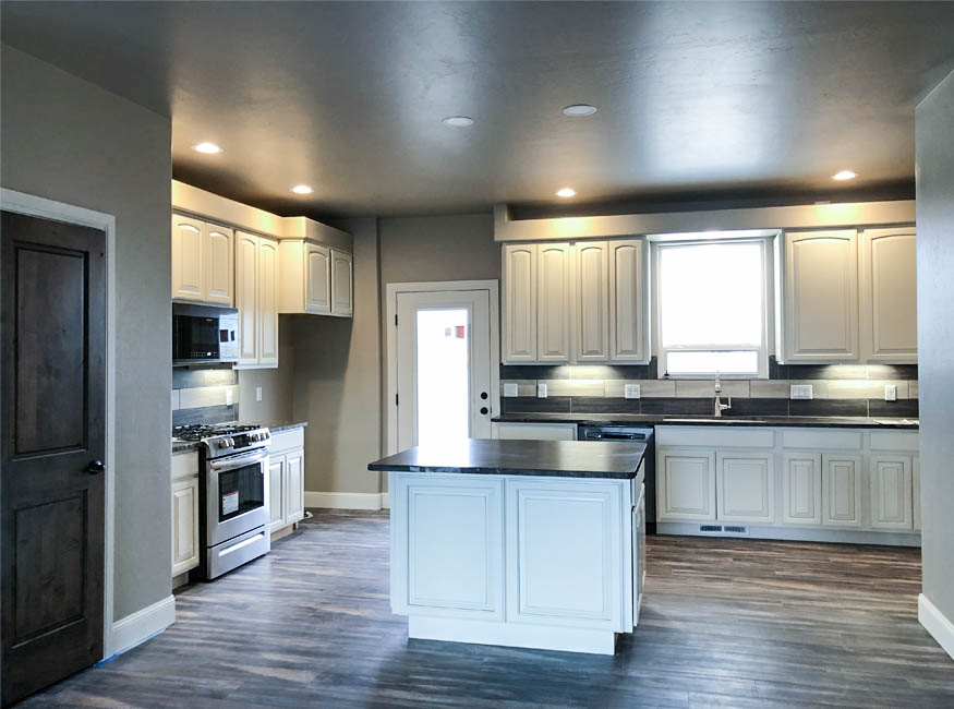 The kitchen of 853 Fire Agate has modern glazed white cabinetry and dark quartzite countertops.