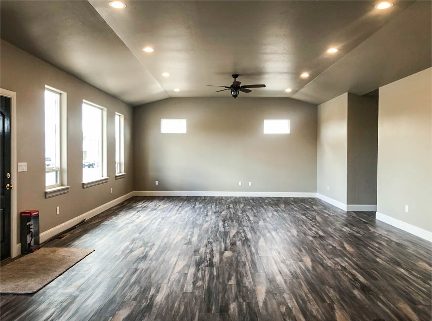 The living room of 853 Fire Agate has a coved ceiling with a ceiling fan and recessed lighting. The clerestory windows on the south end allow natural light, while maintaining privacy and minimizing heat. The large east facing windows look over the front yard.