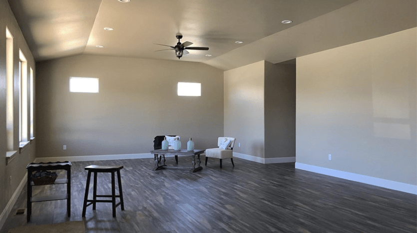 The living room of 853 Fire Agate has LVP flooring, greige walls, and white trim. The large windows face east, allowing lots of natural light, and the south facing clerestory windows allow light without adding heat.