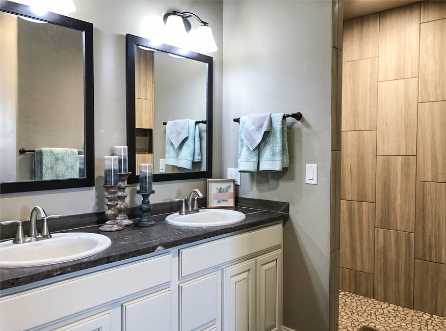 The master bath of 853 Fire Agate includes a step-in shower with a shampoo cubby, double sink vanity, and private toilet room with a built-in linen closet.