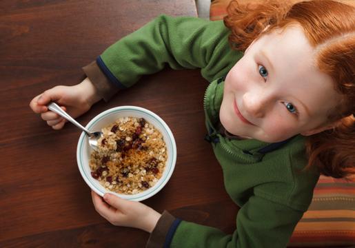 Girl eating bowl of oatmeal