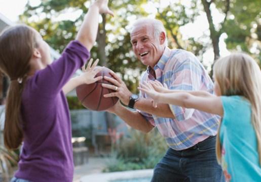 Kids and their grandfather playing basketball