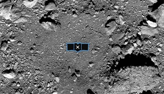 A picture looking down on the surface of Bennu, showing a flat dusty target area surrounded by a ring of bigger rocks and rubble.