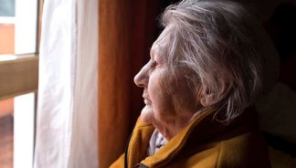 Older woman with depression looking out a window