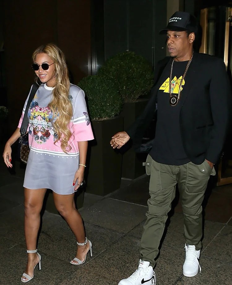 Jay Z styles fatigue pants and a graphic tee with the Supreme x Nike Air Force 1 High.