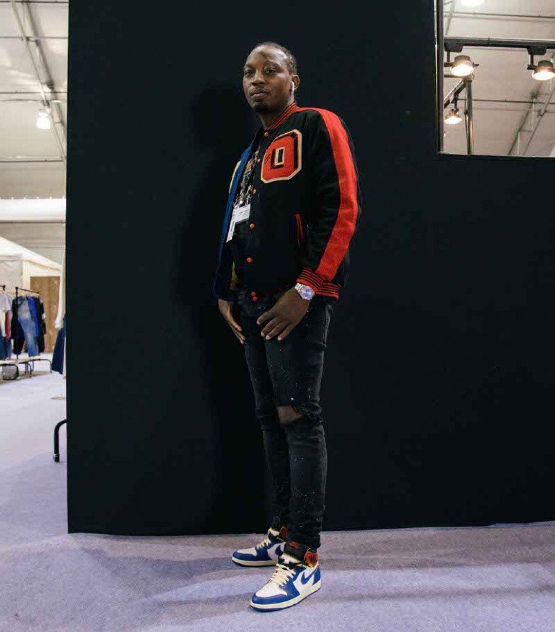 Color coordinating black skinny jeans, a letterman jacket, and a graphic tee with the Union x Air Jordan 1.