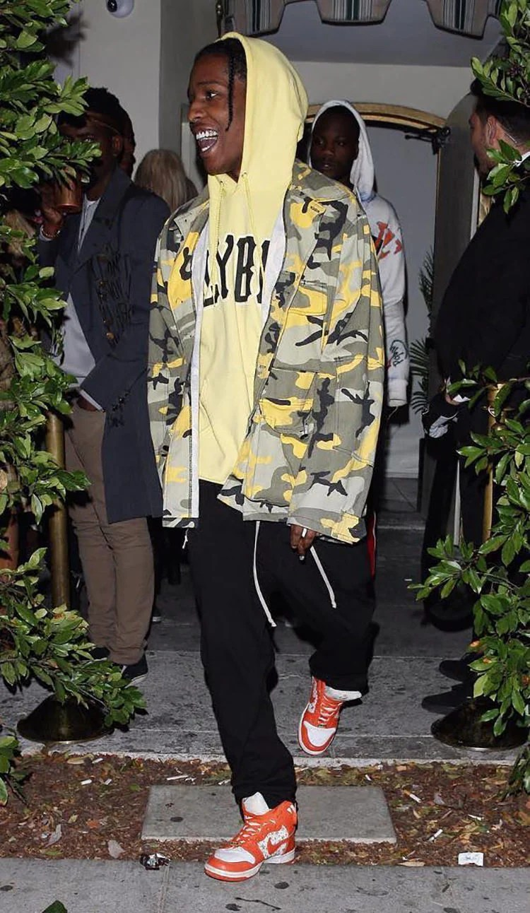 ASAP Rocky pairs the Supreme x Nike SB Dunk High with loose sweats, a graphic hoodie, and a camo jacket.