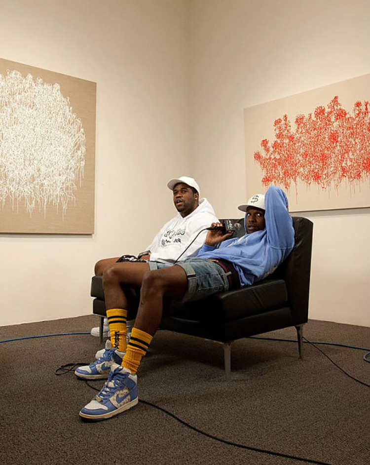 ASAP Rocky pairs a matching hoodie and denim shorts with the Supreme x Nike Dunk High.