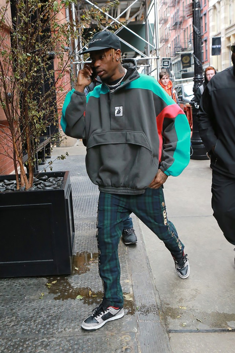 Travis Scott pairs an anorak jacket with tailored plaid trousers and the Supreme x Nike SB Dunk Low.