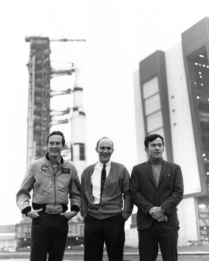 Charlie Duke, Ken Mattingly, and John Young pose in front of the Vehicle Assembly Building during the second rollout of Apollo 16
