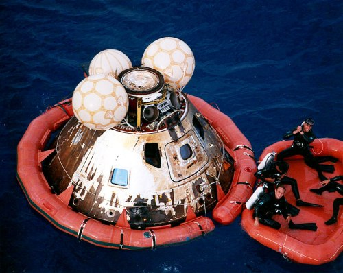 Navy divers pose with the Command Module before it is hoisted aboard the Iwo Jima.