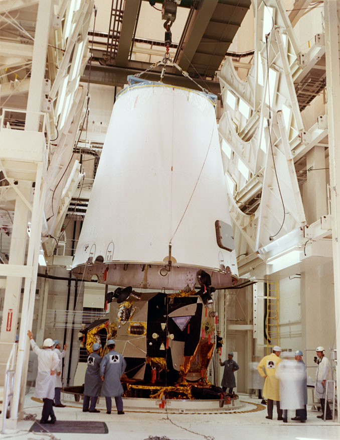 The third stage adapter is lowered into place over the Lunar Module during stacking in the Vehicle Assembly Building