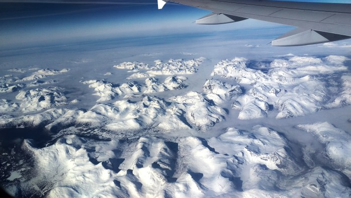 Frozen Fjords and cloud top mountains of Norway. Taken from the plane with mobile phone.