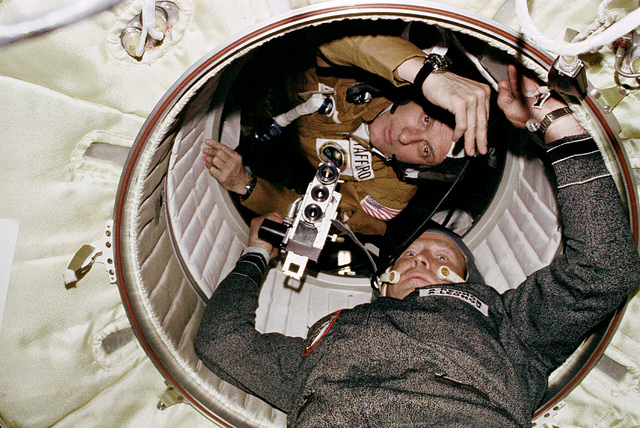 Astronaut Thomas P. Stafford and cosmonaut Aleksei A. Leonov are seen at the hatchway leading from the Apollo Docking Module (DM) to the Soyuz Orbital Module (OM) during the joint U.S.-USSR Apollo Soyuz Test Project (ASTP