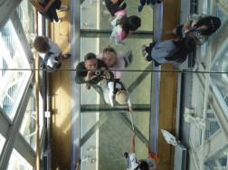 Bad husband forcing wife onto glass walkway