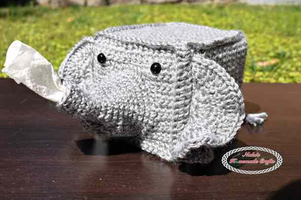 Crocheted grey elephant tissue box cover on a dark wooden surface on a grass background