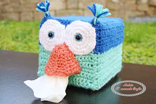Crocheted Blue Owl with a orange nose that has tissues coming out sitting on a wooden table on grass
