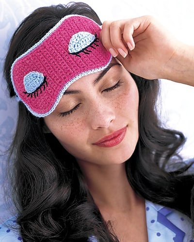 Crocheted pink eye mask with sleepy eyes displayed worn by a women with brunette hair and blue pajamas