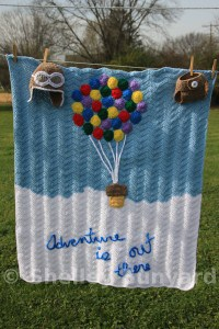 Crocheted blue and white blanket with lots of colorful balloons as hot air ballon hanging on a clothline