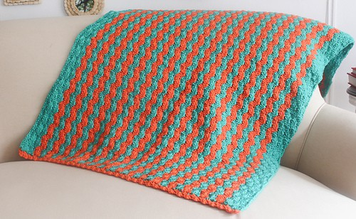 Crocheted orange and blue rippled blanket on a beige couch in a living room