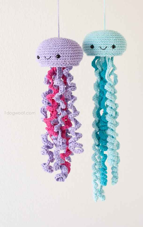 Crocheted pink purple and blue jellyfish hanging in front of a white wall